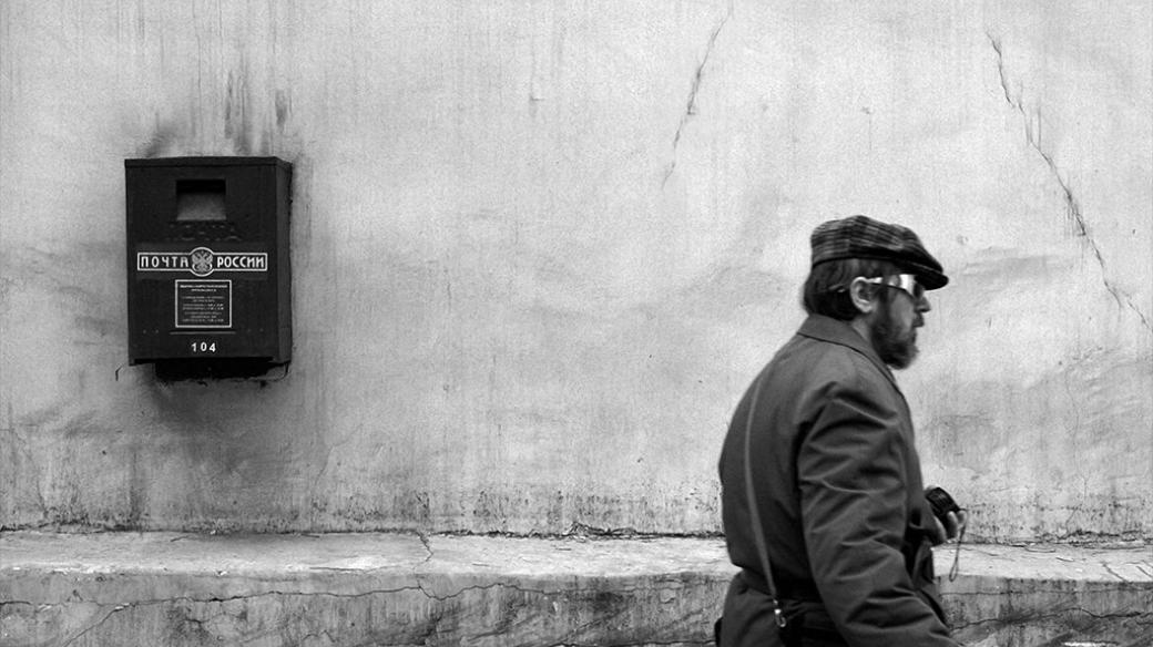 A man passes a mailbox hanging on the wall, Moscow, Russian Federation