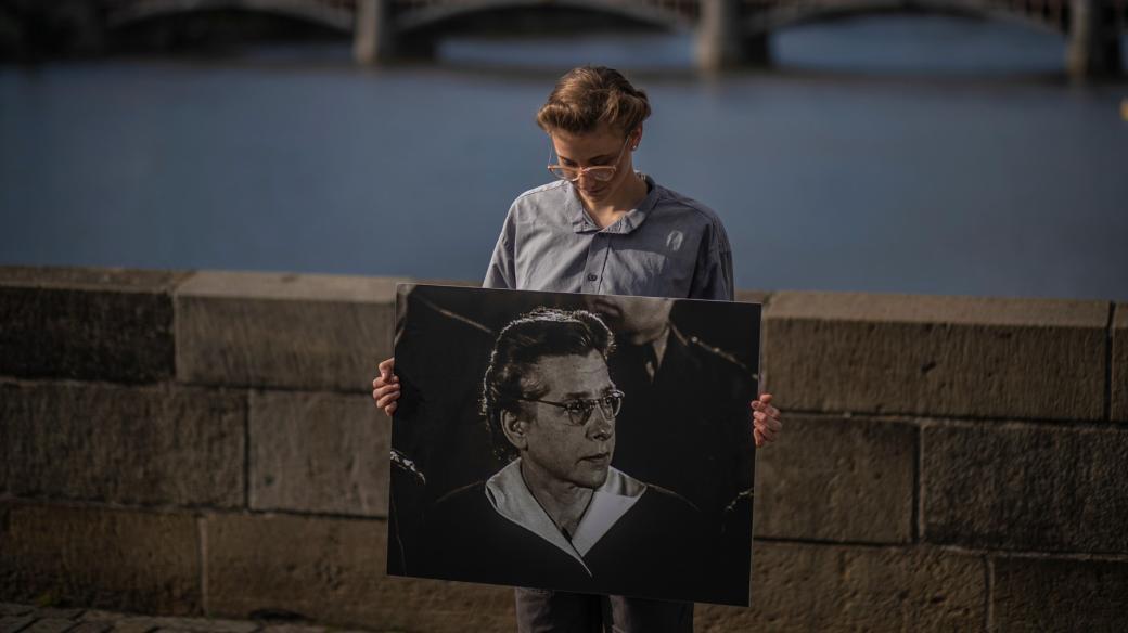 Studentka na Karlově mostě drží portrét Milady Horákové při příležitosti 70. výročí její popravy