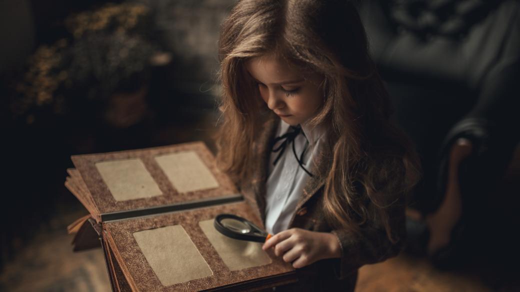 Dítě, dívka v převleku Sherlocka Holmese, fotoalbum, lupa, starý interiér