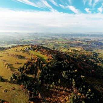 Rozhledna na vrchu Kozákov v Českém ráji na leteckém snímku. V pozadí uprostřed hrad Trosky