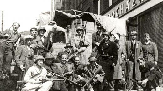 Bojovníci pražského povstání vyzbrojení puškami, pancéřovými pěstmi, sedící muž uprostřed italským samopalem Bereta a vpravo dole je lehký kulomet vz.26